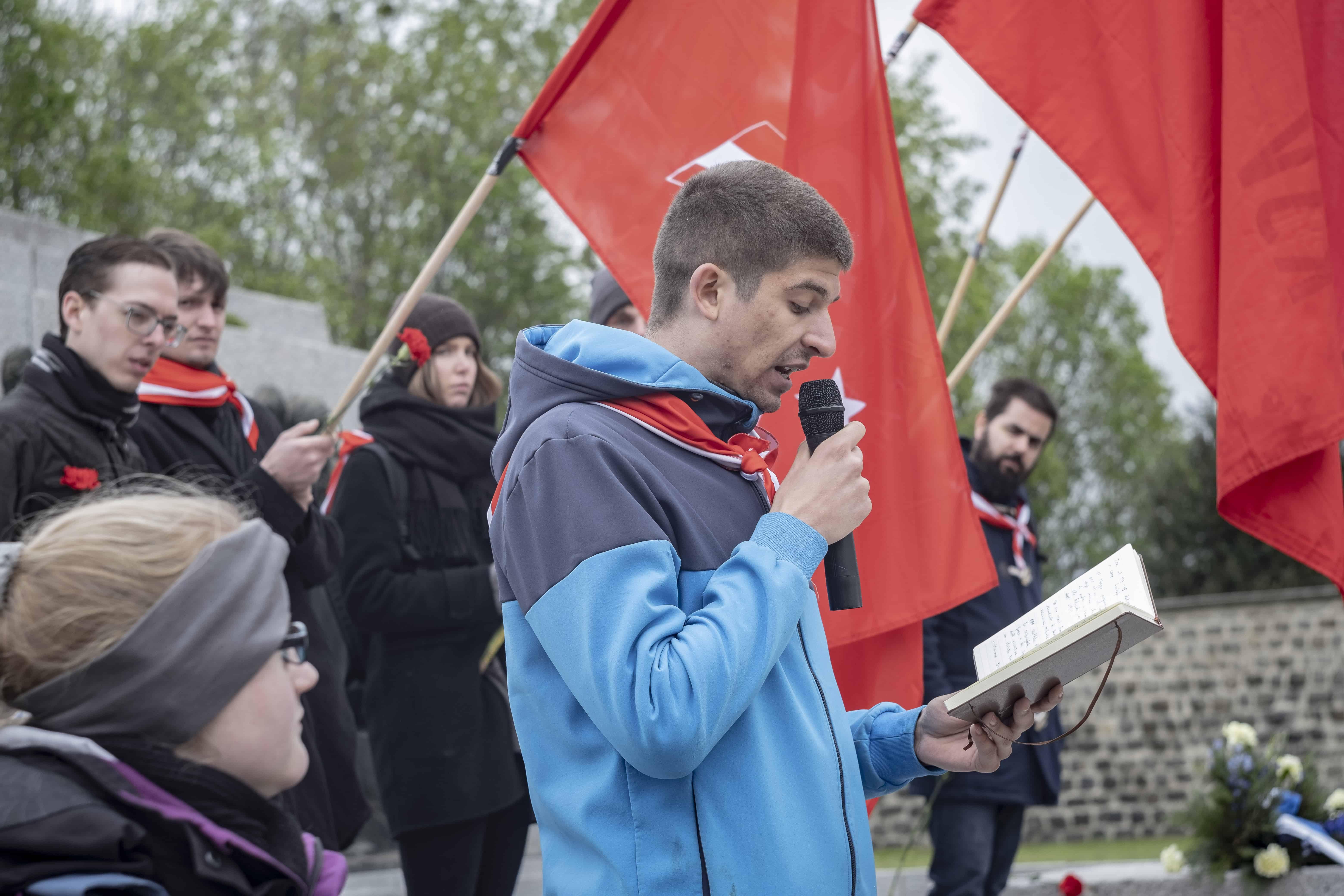 Redner vorne, rote Fahnen im Hintergrund